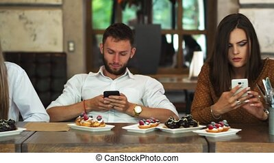 groupe, restaurant, séance, regarder, téléphone, multi-ethnique, chaque, amis, ton, ennui