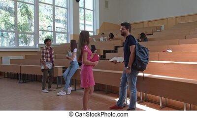Groupmates talking at university classroom. - Group of few...