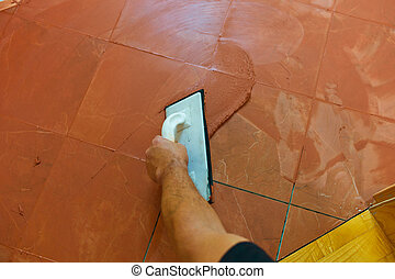 grout is applied - a tiler carries on floor tiles on the ...
