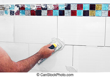 Grouting tiles - Man grouting wall ceramic tiles with float