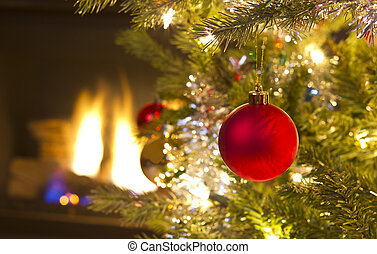 Bright red Christmas ornament hanging on Xmas Tree with fire place in background
