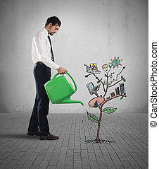 Growing the economy - Businessman watering a plants with...
