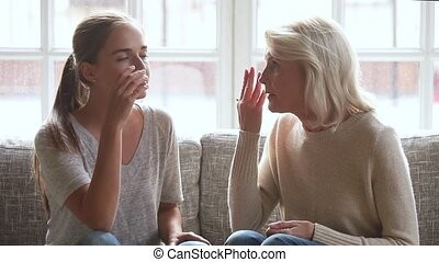 Grown up daughter and elderly mother talking having...