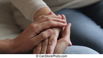 Close up compassionate young woman stroking hand on middle aged mature mom, having trustful conversation indoors. Kind grown up devoted daughter supporting senior old mother, showing love care.