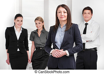 Grown up Successful business woman holding hands together. Young Smiling business people standing on blur background