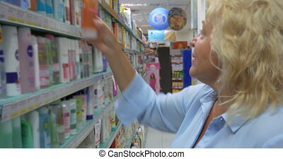 Grown woman in the store of city of Perea, Greece chooses goods from the shelf