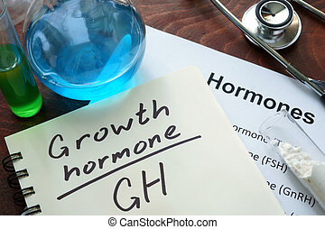 growth hormone written on notebook. Test tubes and hormones list.