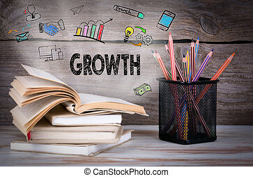 Growth. Stack of books and pencils on the wooden table.