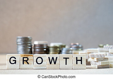 Growth Word Written In Wooden Cube on wood table with money stack up as graphs in background