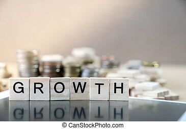 Growth Word Written In Wooden Cube reflection on black mirror with coins stack as graph in background