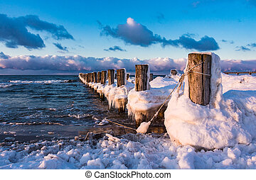 Groyne on shore of the Baltic Sea in winter.