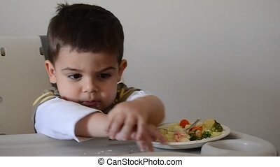Grumpy two years old boy playing with food and refusing to eat