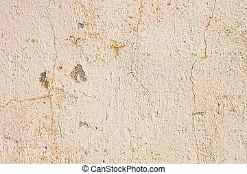 Grunge background of cracked cloud peeled putty wall in beige tones.