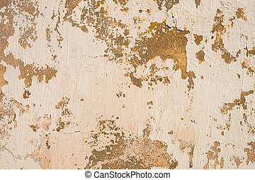 Grunge background of cracked peeling walls with peeled putty in beige tones.