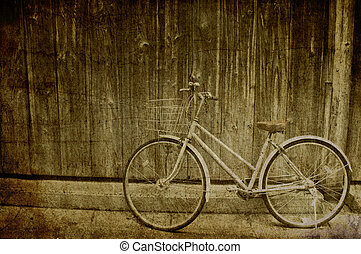 Grunge background of vintage bicycle with wooden wall