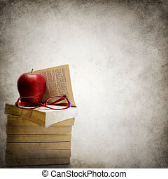Grunge background with stack of books, apple and eyeglasses