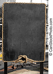 Grunge blackboard with rope frame outdoor as a background for your message