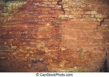 Grunge brick wall with peeling orange paint