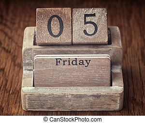 Grunge calendar showing Friday the fifth on wood background