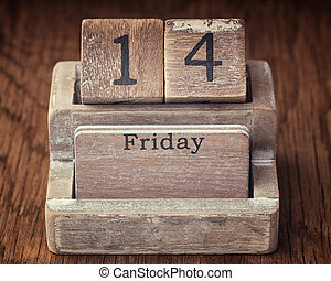 Grunge calendar showing Friday the fourteenth on wood background