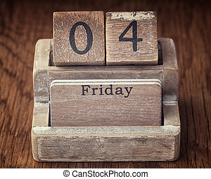 Grunge calendar showing Friday the fourth on wood background