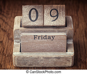 Grunge calendar showing Friday the ninth on wood background