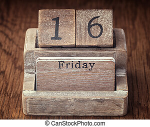 Grunge calendar showing Friday the sixteenth on wood background
