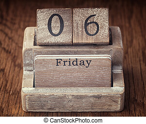 Grunge calendar showing Friday the sixth on wood background