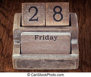 Grunge calendar showing Friday the twenty eighth on wood background