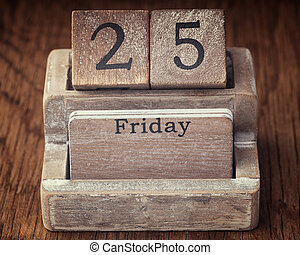 Grunge calendar showing Friday the twenty fifth on wood background