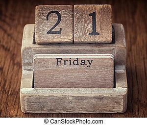 Grunge calendar showing Friday the twenty first on wood background