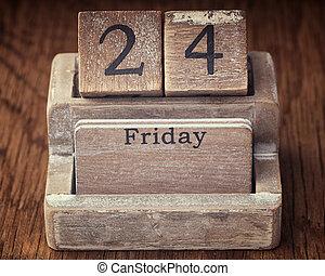 Grunge calendar showing Friday the twenty fourth on wood background