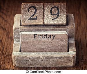 Grunge calendar showing Friday the twenty ninth on wood background