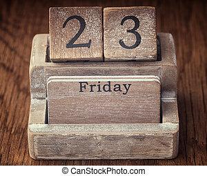 Grunge calendar showing Friday the twenty third on wood background