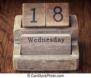 Grunge calendar showing Wednesday the eighteenth on wood background