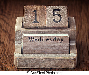 Grunge calendar showing Wednesday the fifteenth on wood background