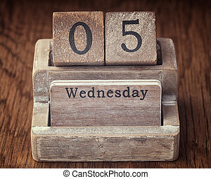 Grunge calendar showing Wednesday the fifth on wood background