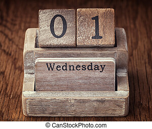 Grunge calendar showing Wednesday the first on wood background