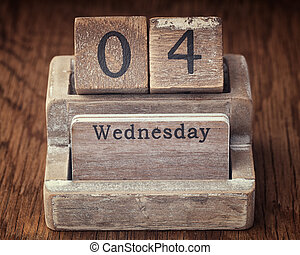 Grunge calendar showing Wednesday the fourth on wood background