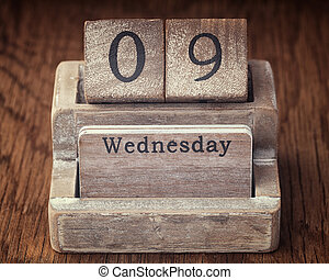 Grunge calendar showing Wednesday the ninth on wood background