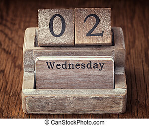 Grunge calendar showing Wednesday the second on wood background