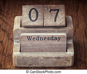 Grunge calendar showing Wednesday the seventh on wood background