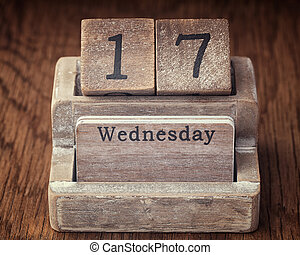Grunge calendar showing Wednesday the seventieth on wood background