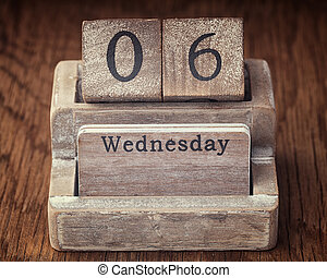 Grunge calendar showing Wednesday the sixth on wood background