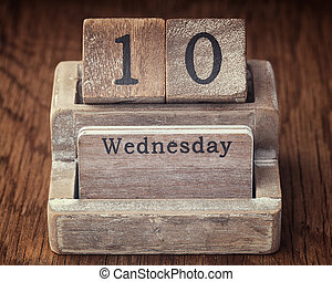 Grunge calendar showing Wednesday the tenth on wood background