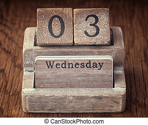 Grunge calendar showing Wednesday the third on wood background