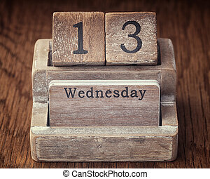 Grunge calendar showing Wednesday the thirteenth on wood background