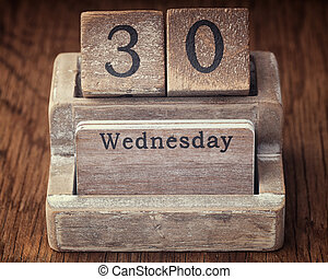 Grunge calendar showing Wednesday the thirtieth on wood background