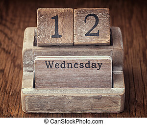 Grunge calendar showing Wednesday the twelfth on wood background