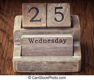 Grunge calendar showing Wednesday the twenty fifth on wood background